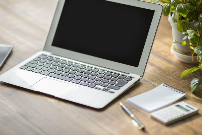 木目調のテーブルに置かれたノートパソコン