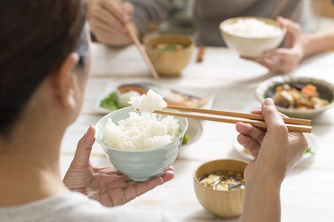 箸と茶わんでご飯を食べている女性