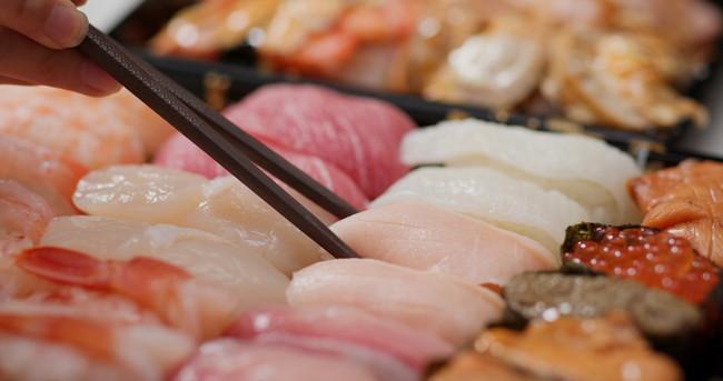 黒い箸で握り寿司を取るところ
