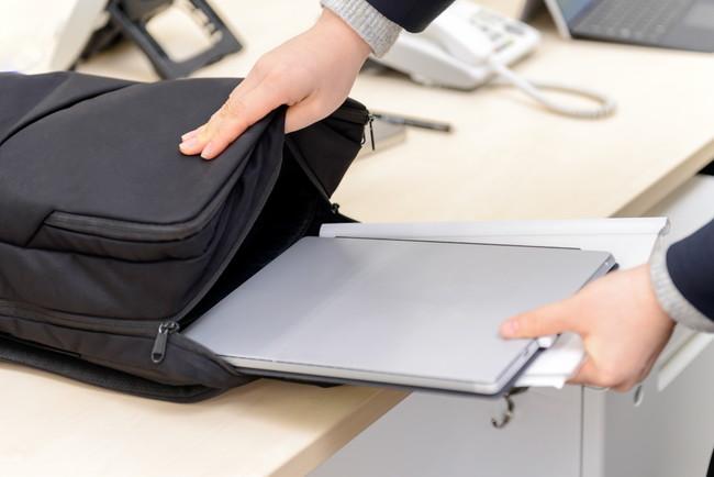 ノートパソコンをカバンに入れるビジネスマン