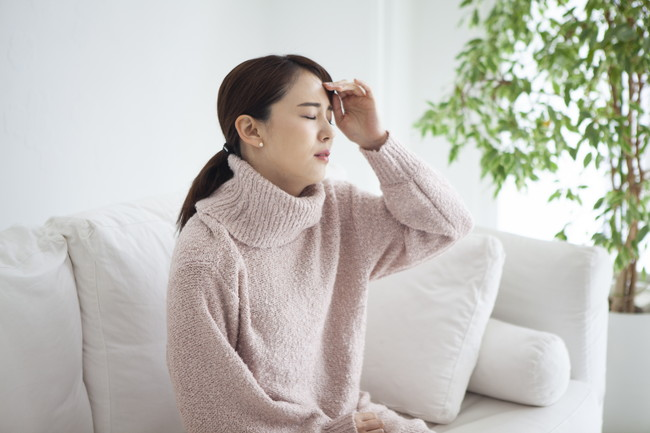 自宅のソファに座り頭痛で具合が悪そうな女性