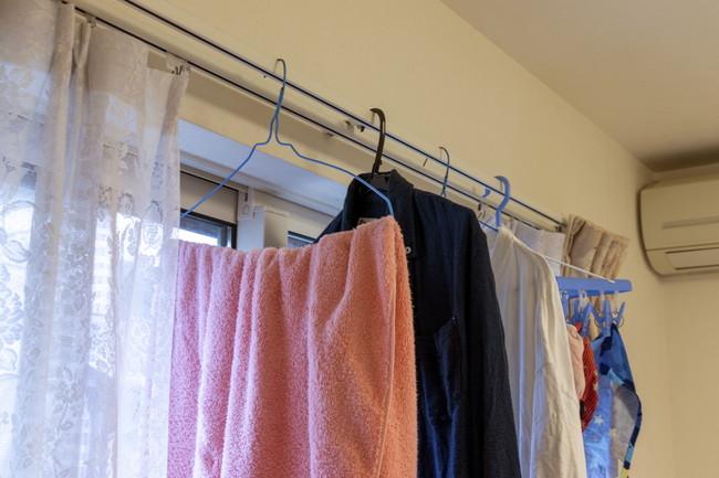 カーテンレールにかけて部屋干ししている洗濯物