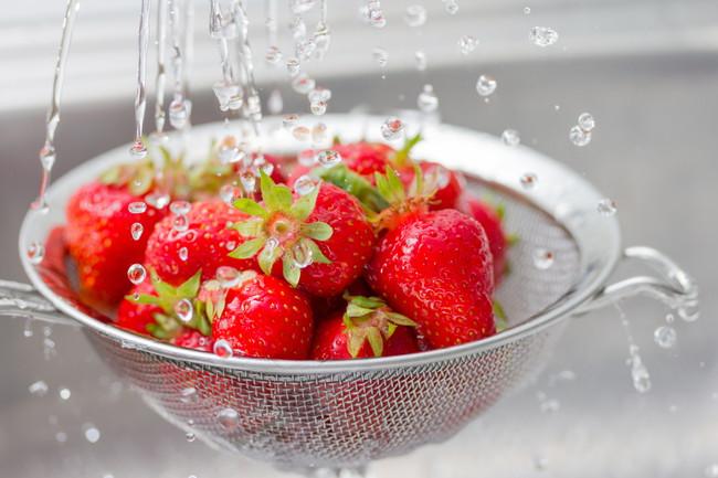 ザルでヘタ付きのままイチゴを洗っている
