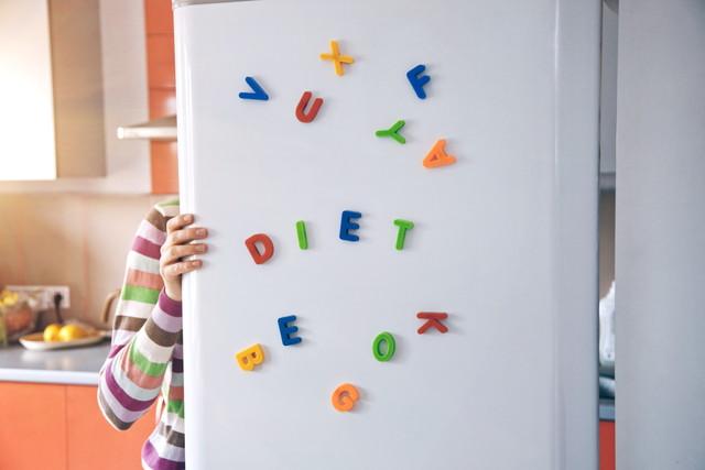 文字が貼り付けられた冷蔵庫の扉を開けている様子