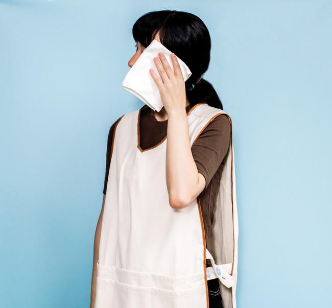 汗を拭くエプロン姿の女性