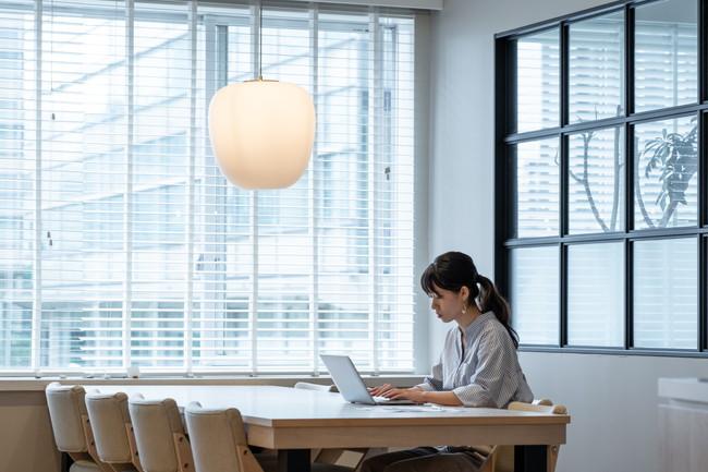 大きなデスクで1人パソコンをしている女性