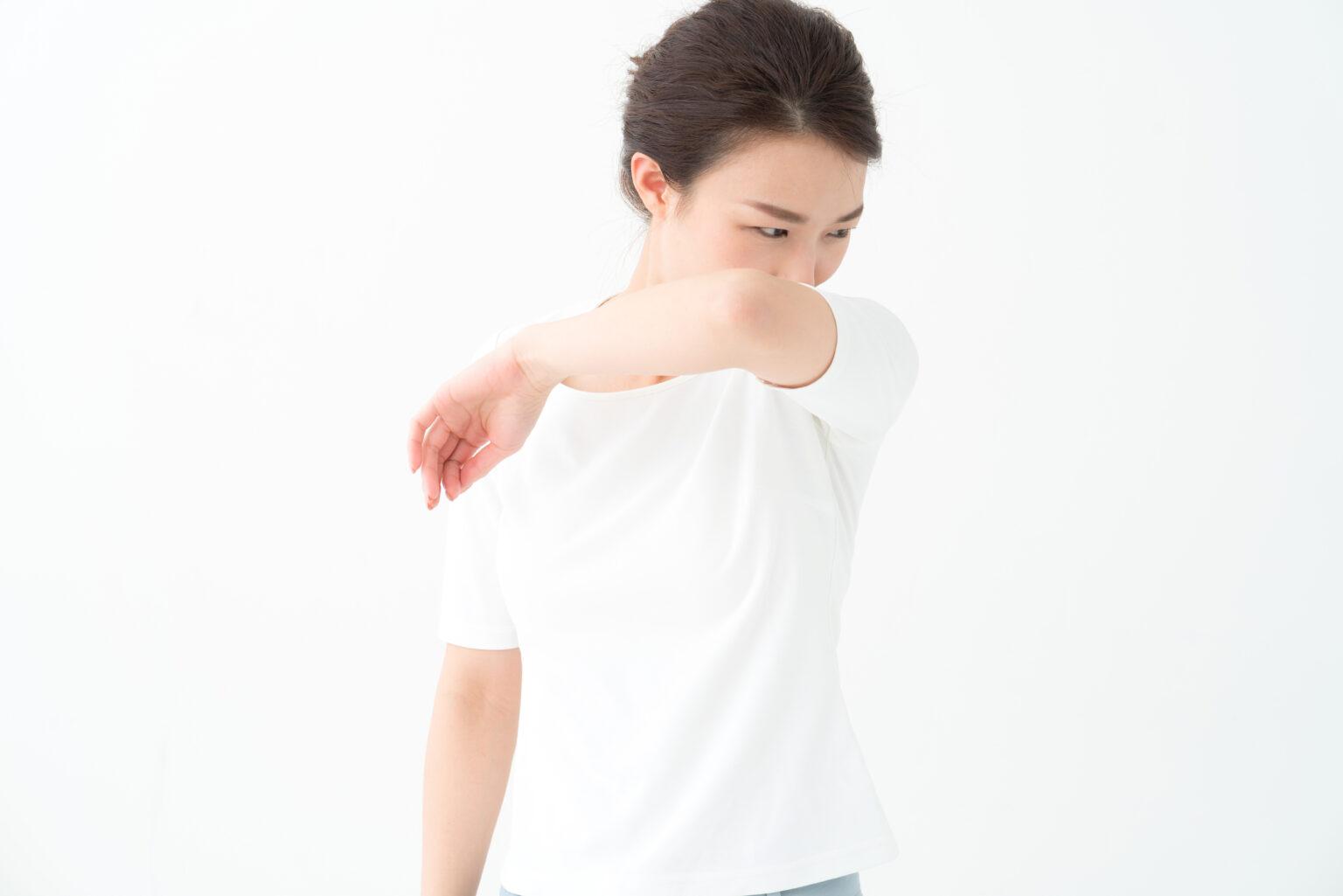 着ている白いTシャツの臭いをかぐ女性