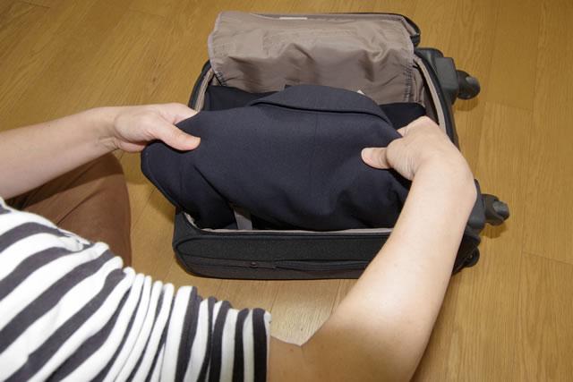 スーツケースに服を入れているシーン