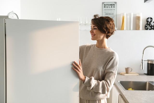 冷蔵庫を開ける笑顔の女性