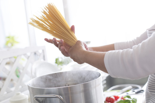 パスタを両手で持って鍋に入れようとしているところ