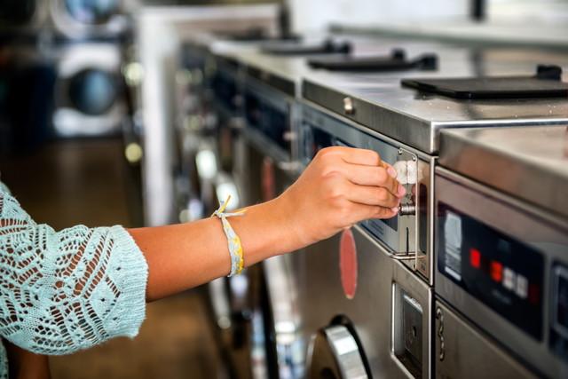 洗濯機にコインを入れる