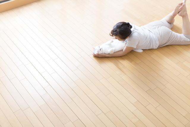 床で猫と遊ぶ女性