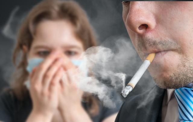 タバコの煙に苦しむ女性