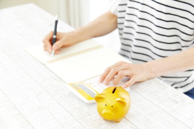 家計簿をつけている女性と豚の貯金箱