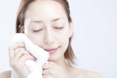 頬にタオルを当てる女性