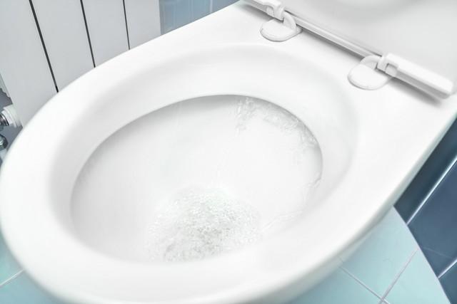 水が流れている便器