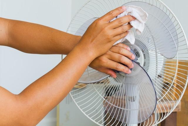 汚れた扇風機を掃除する人
