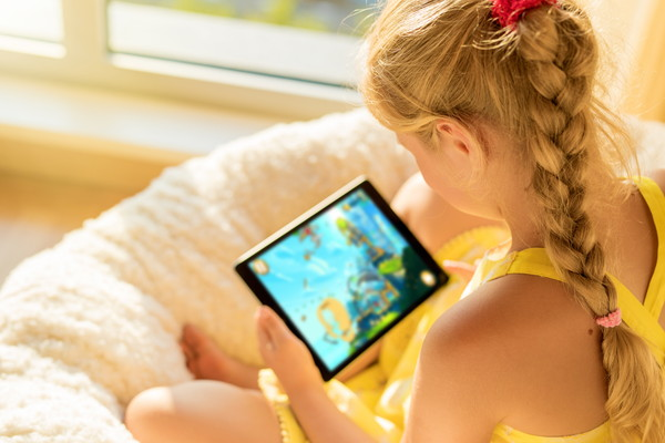 タブレットコンピュータでゲームをしている女の子